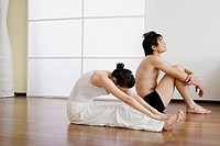 Young couple in yoga attitude, indoors