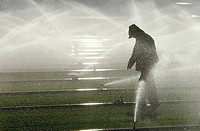 Man in raincoat irrigating farm field, Oxnard, California, USA