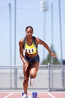 African female runner leaving starting block (thumbnail)
