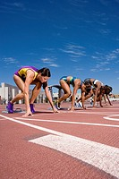 Female runners at starting block kneeling on race track (thumbnail)