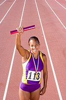 African female athlete with gold medal and relay race baton
