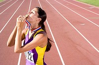 Female athlete kissing gold medal on race track