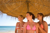 Teenage girls posing under beach umbrella (thumbnail)