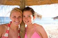 Teenage girls posing under beach umbrella
