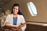 Businesswoman with folder on aeroplane, smiling, close_up
