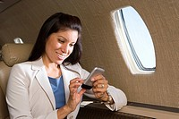 Businesswoman using electronic organiser on aeroplane, smiling, close_up