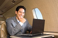 Businessman using laptop computer on aeroplane, smiling, close_up