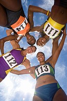 Small group of female athletes arm in arm forming circle, smiling, portrait, view from below