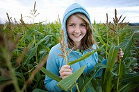 Teenage girl 16_18 wearing hood in corn field, smiling, portrait