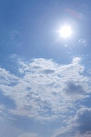 Sun shining in blue sky with clouds