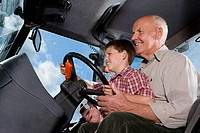 Farmer and grandson driving tractor
