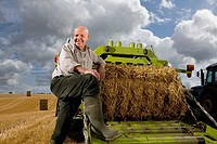 Portrait of farmer leaning on machinery with straw bale