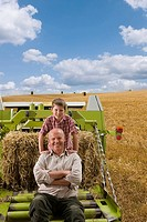 Portrait of farmer and grandson sitting on tractor with straw