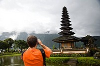 Male tourist photographing Pura Danu Beratan temple, Bali, Indonesia