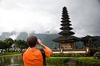 Male tourist photographing Pura Danu Beratan temple, Bali, Indonesia