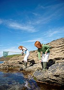 2 girls fishing in rock pool