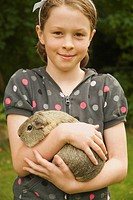 Girl holding a guinea pig, smiling