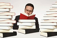 Young man surrounded by books (thumbnail)