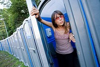 Young woman, wearing sunglasses, inside a portable toilet