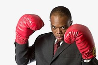 Young black business man with red boxing gloves in studio white background Denver, Colorado, USA