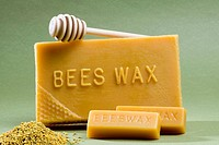 Honey bee products beeswax bars, bee pollen and honey dipper in studio