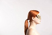 Young redhaired woman with golden mask