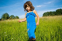 A girl walking through a field of long grass
