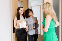 A woman greeting friends at the door