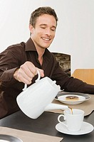 A man pouring coffee into a coffee cup