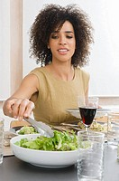 A woman serving herself salad