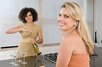 A woman opening a bottle of wine for a friend