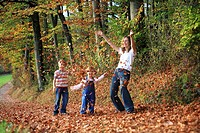 Mother with daughter and son playing with leaves in fall, having fun, autumn foliage covering path in forest, autumn, fall, Zuerich, Switzerland