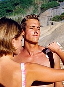 Rear view of a young woman pouring suntan lotion on a young man´s chest