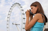 Side profile of a young woman taking a photograph in front of a ferris wheel