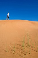 Woman walking on dune, Arabian Desert, United Arab Emirates