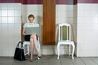 Businesswoman Using Laptop in Waiting Room