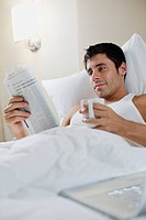 Man Lying in Bed Reading and Drinking Coffee