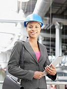 Businesswoman wearing hard_hat in warehouse