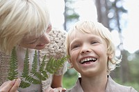 Mother tickling son with fern leaf