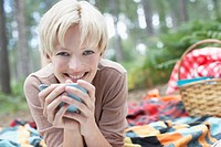 Woman drinking coffee at campsite