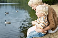 Mother and son feeding ducks in pond