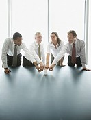 Businesspeople touching cup together at conference table (thumbnail)