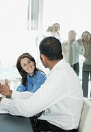 Co_workers watching businesspeople having meeting in conference room