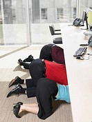 Businesspeople hiding under desk in office