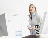 Businesswoman sitting on desk drinking coffee