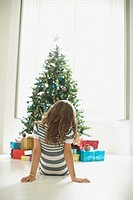 Girl waiting to open Christmas gifts