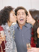 Women kissing man at Christmas party