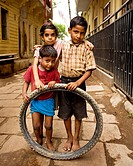 three poor kids in india playing with a tire