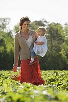 Mother and baby daughter picking strawberries