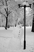 Snowman In A Park Next To A Lamp Post